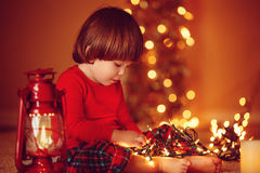 Baby playing with Christmas light Royalty Free Stock Image