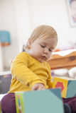 Baby playing color boxes Stock Images