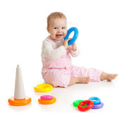 Baby playing with color pyramidion. Child playing with color toy over white background Royalty Free Stock Photography