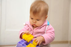 Baby playing with colored constructor. Baby sitting and playing with colored constructor Stock Photos