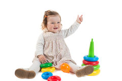 Baby is playing with colored toy pyramid Royalty Free Stock Images
