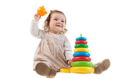 Baby is playing with colored toy pyramid Royalty Free Stock Photography