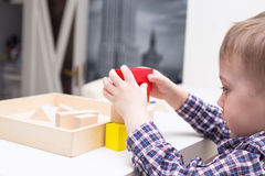 Baby playing with colored wooden cubes Stock Images