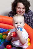 Baby playing with colorful balls Stock Photos