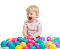 Baby playing among colorful balls Stock Images