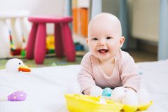 Baby playing with colorful toys at home. Royalty Free Stock Photography