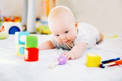 Baby playing with colorful toys at home. Stock Photos
