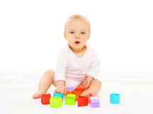 Baby playing with colorful toys on white background Stock Image
