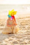 Baby playing with colorful windmill toy on beach Stock Photography