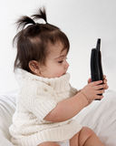 Baby playing with cordless phone. Adorable baby girl in white dress playing with phone Stock Photos
