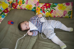 Baby playing in cot. Young male baby playing with electrical device in cot Royalty Free Stock Images