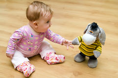 Baby playing with cuddly toy Stock Photo