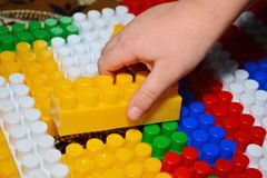 Baby playing and discovery with colorful toys at home, close-up detail. Child plays with plastic building blocks royalty free stock photos