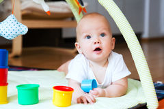 Baby playing and discovery. Baby playing with colorful toys at home. Happy 6 months old baby child playing and discovery Royalty Free Stock Photography
