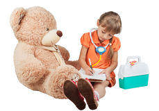 Baby is playing doctor, treats a bear Stock Photography
