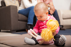 Baby playing with a doll under supervision Stock Photos