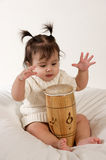 Baby playing with drum. Adorable baby girl playing drum isolated on white Royalty Free Stock Images