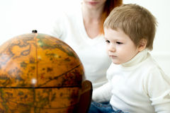 Baby playing with earths globe Stock Images