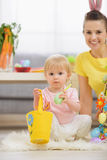 Baby playing with Easter decorations Stock Photos