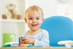 Baby playing education toy at table in nursery Stock Photography