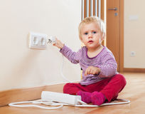 Baby playing with electrical extension. And outlet on floor Stock Photo
