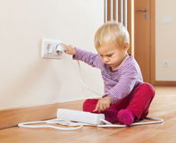 Baby playing with electrical extension Royalty Free Stock Image