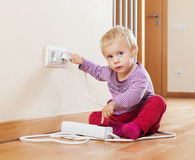 Baby playing with electrical extension and outlet Royalty Free Stock Photo