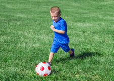 Baby playing football in the meadow Stock Photos