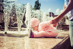The baby is playing at the fountain stock images