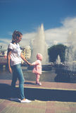 The baby is playing at the fountain stock photo