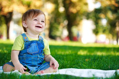 Baby is playing on the green grass Royalty Free Stock Image
