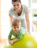 Baby playing with gymnastic ball with mother at home. Baby boy playing with gymnastic ball with mother at home Royalty Free Stock Photo