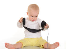 Baby  playing with headphones on white background Royalty Free Stock Image