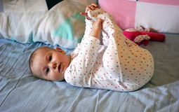 Baby playing with her feet royalty free stock image
