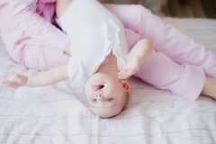 Baby is playing on her mother`s lap in the bedroom. On the bed Stock Photography
