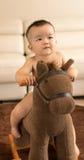 Baby playing hobbyhorse Royalty Free Stock Image