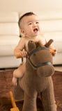 Baby playing hobbyhorse Royalty Free Stock Photos