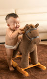 Baby playing hobbyhorse Royalty Free Stock Photo