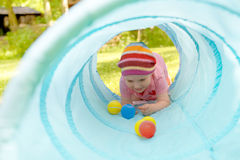 Baby playing inside a toy tunnel Royalty Free Stock Photos