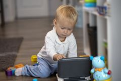 Baby playing and investigating on a toy laptop royalty free stock image