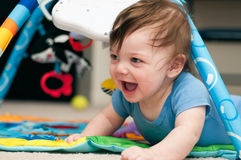 Baby playing on a jungle mat Stock Photos