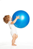 Baby playing with a large fitness ball. Royalty Free Stock Photos