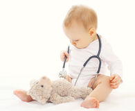 Baby playing and listens stethoscope Stock Photos