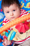 Baby playing with mobile. Cute baby boy in colorful chair playing with educational mobile toys Royalty Free Stock Images