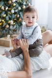 The baby is playing with mother near Christmas tree Stock Image