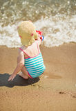 Baby playing near sea. Rear view Stock Photos