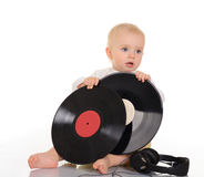 Baby playing with old vinyl record and headphones Royalty Free Stock Image