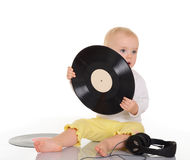 Baby playing with old vinyl record and headphones Royalty Free Stock Photography