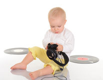 Baby playing with old vinyl record and headphones Stock Image