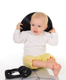 Baby playing with old vinyl record and headphones Stock Photos